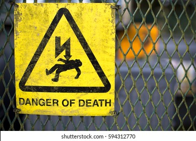 A yellow sign warning of danger of death through electrocution attached to a metal grille fence