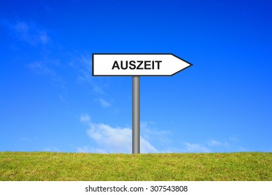 Yellow signpost on green grass showing time out in german language in front of blue sky