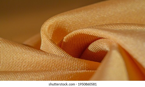Yellow silk. Smooth elegant yellow luxurious silk fabric can be used as an abstract background with copy space, close up. colorful texture