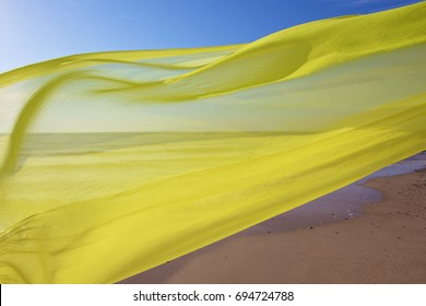 yellow silk tissue flying over the sea and sky background