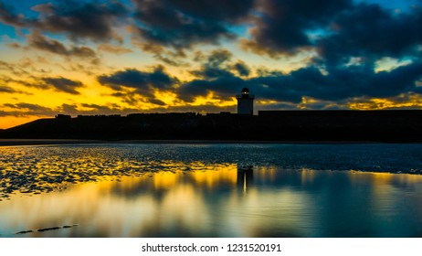 Yellow sky and dark clouds reflecting in the water at Burry Port beach, with the lighthouse in the distance.  Carmarthenshire. Wales. UK.