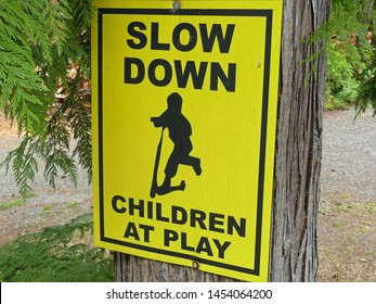 "Yellow ""slow down children at play"" sign on a Western Red Cedar"