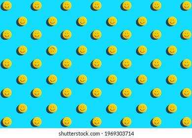 Yellow smiley face cookie, food, flat lay, top view, copy space on blue background. Be different.
