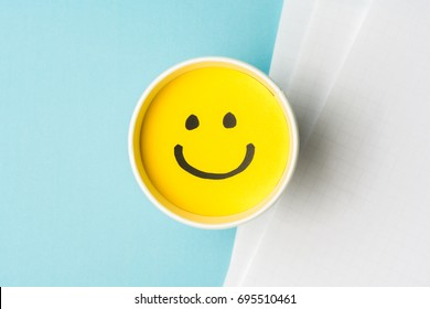 Yellow smiley face or happy emotion at work, on paper cup and papers over blue background. Happy work day concept.