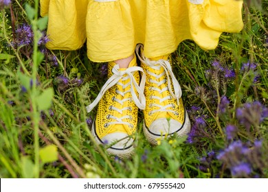 Yellow sneakers in the grass. Beautiful young girl in a yellow dress a blooming summer field. Girl in purple flowers outdoors in summer