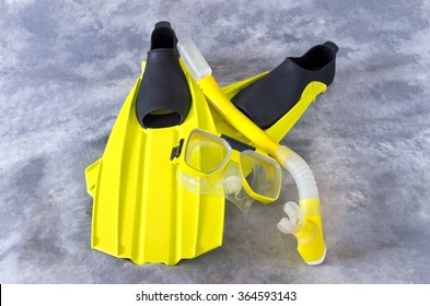 yellow snorkel mask and fins snorkeling gear isolated against gray background