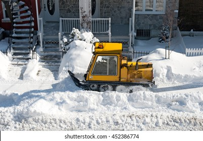 Yellow snowplough removing snow in the residential area of the city.