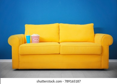 Yellow sofa with popcorn and drink in home cinema. Watching movie