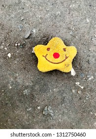 Yellow soft toy-smile lies on the gray sidewalk.