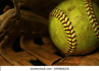 Yellow softball in a brown glove.