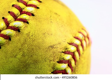 Yellow softball closeup with red seams.