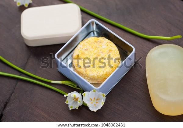 Barras de jabón sólido amarillo y plumas de champúBarras de jabón sólido amarillo y champú dentro de un contenedor de metal reutilizable. Fabricado con ingredientes naturales y amigables con la piel. Para un baño sin desperdicios, sin plástico y