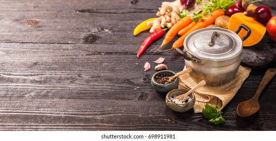 Yellow soup in an old aluminum saucepan on black rustic table, top view,  Homemade food, cooking, vegetarian concept, copy space