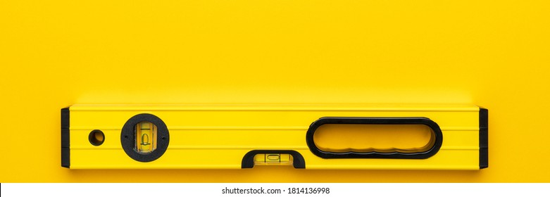 Yellow spirit level on the yellow background. Panoramic photo of bubble level with some copy space. - Shutterstock ID 1814136998