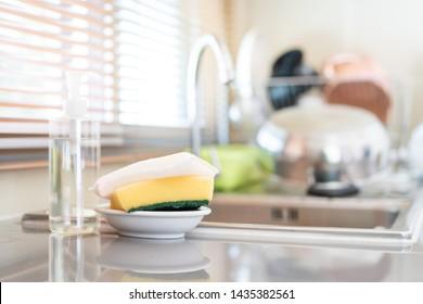 Esponjas amarillas y jabón líquido lavavajillas en el lavabo sucio completamente con platos y utensilios de cocina.