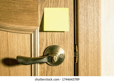 a yellow square piece of paper for notes and reminders is pasted on the door