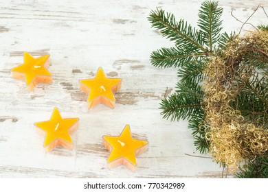 yellow starry tea lights with fir branch