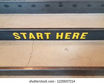 yellow start here sign on black and grey cement stairs