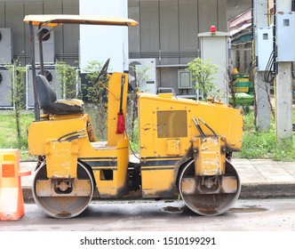 Yellow Steamroller parked on the construction site.