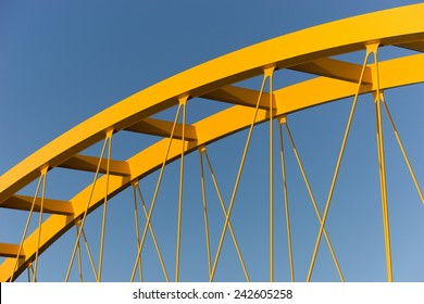 Yellow steel cable stayed bridge against a steel blue sky