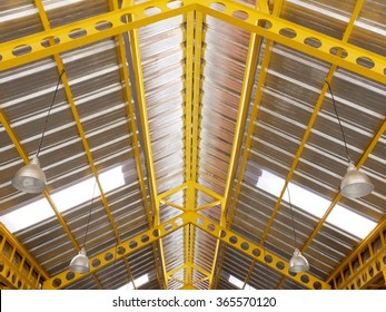 Yellow steel under roof structure with lighting system.