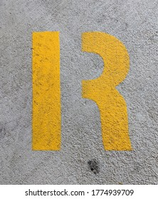 Yellow stencil letter R on a grey concrete background