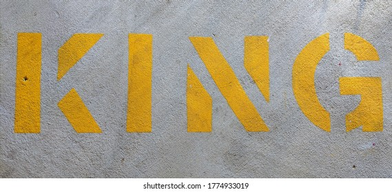 Yellow stencil letters KING on concrete