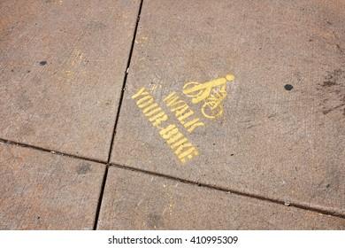 Yellow stencil on city sidewalk saying Walk your bike