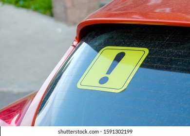 Yellow sticker with an exclamation point on the car's glass. A newbie driver's sign. Close up.