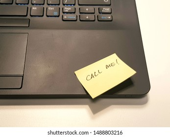 "Yellow sticker notes on a black laptop with handwritten word ""call me!"""
