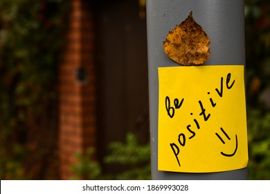 yellow sticker with the words be positive and red autumn maple leaf glued on a gray concrete pillar against the background of a red brick fence and a gate