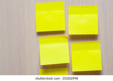 yellow stickers on a wooden background.