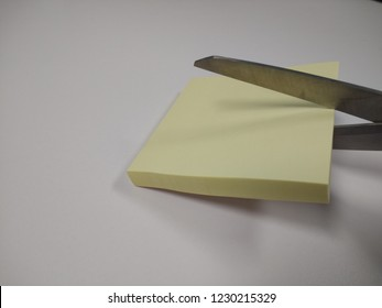 Yellow sticky note pads isolated with scissors