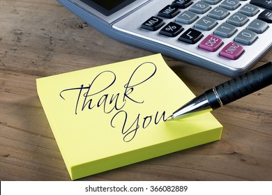 "Yellow sticky note with ""Thank you"" written with pen. Administrative Professionals or Secretaries day concept."
