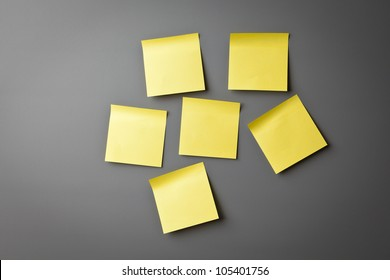 Yellow sticky notes on a grey wall