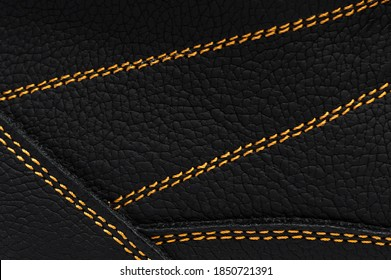 Yellow stitches on the leather of boots. Macro photo.