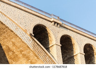 yellow stone bridge with solid arches for railway track