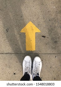 Yellow straight arrow sign and white shoes. Straight direction concept