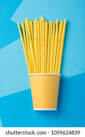 Yellow straws for a party in paper cups on a bright blue background