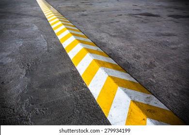 A yellow stripe speed ramp on concrete road.