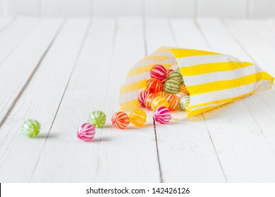 Yellow striped candy bag spilling its candies over a white wooden table