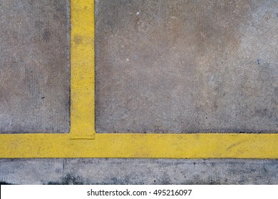 Yellow stripes perpendicular on the cement floor.