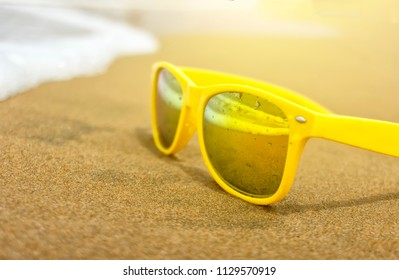 yellow stylish sunglasses on the beach in the sand and waves