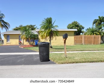 Yellow Suburban Ranch style home with trash container next to mailbox blue sky USA