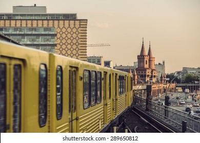 Yellow Subway train on trail to the historical bridge (Oberbaumbruecke) in Berlin, Germany,  Europe, Vintage filtered style