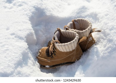 Yellow suede winter boots on white snow on a sunny frosty day.
