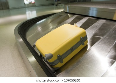 Yellow suitcase on airport carousel