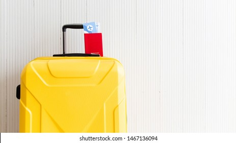Yellow suitcase with Passport Ticket Boarding Pass on white aluminum background with blank space for text. Preparation before going to the airport. Travel&Tourism in vacation concept.