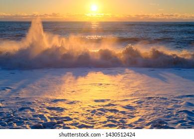 Yellow sun lights big storm waves. Sunset on the sea. Beautiful nature