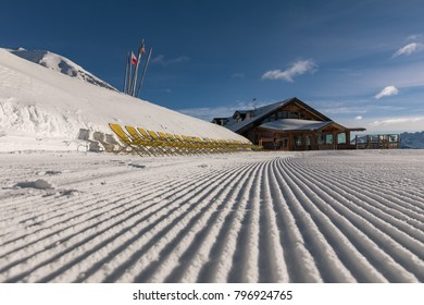 Yellow sun loungers on the slope Dolomites, ski area. Sunny day. Ski area with beautiful slopes. Empty ski slope in winter on a sunny day. Prepared piste in Val di Fiemme